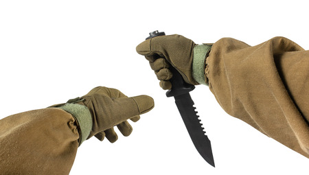 Isolated photo of a first person view arms in tactical jacket and gloves holding upper grip black military and hunting knife on white background.