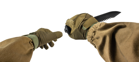 Isolated photo of a first person view arms in tactical jacket and gloves holding vertical grip black military and hunting knife on white background. Stock fotó