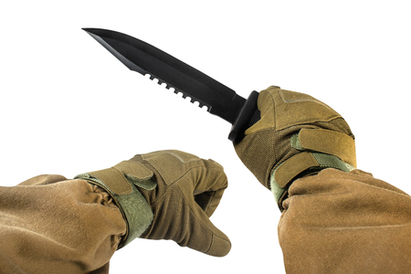 Isolated photo of a first person view arms in tactical jacket and gloves holding black military and hunting knife on white background.