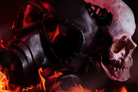 Photo of a black burning military gas mask laying in flames with human skull on black background.