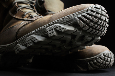 Photo of brown suede military tactical boots with protector texture standing on black surface background close up view.