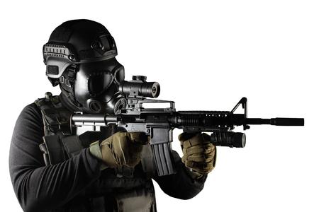Foto de un soldado totalmente equipado con chaleco táctico de armadura negra, máscara de gas, rifle automático, guantes y casco apuntando a la vista de perfil aislado sobre fondo blanco. Foto de archivo