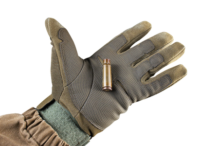 Isolated photo of a first person view palm hand in tactical jacket and gloves holding Ak 47 rifle bullet shell on white background.