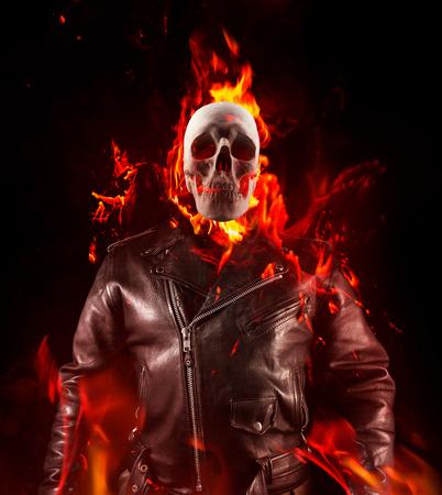 Foto de un esqueleto de demonio en la vista del torso de chaqueta de motorista de cuero negro de pie en el fuego sobre fondo negro.