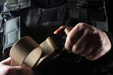 Photo of a fully equipped soldier in black armor tactical vest standing with belt on black background closeup front view.