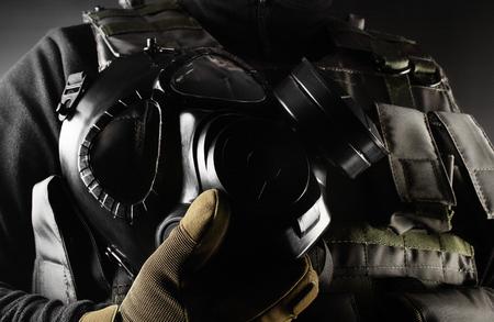 Photo d'un soldat entièrement équipé en gilet tactique d'armure noire et gants debout et tenant un masque à gaz sur fond noir vue d'angle en gros plan. Banque d'images