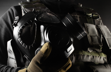 Photo of a fully equipped soldier in black armor tactical vest and gloves standing and holding gas mask on black background closeup angle view.