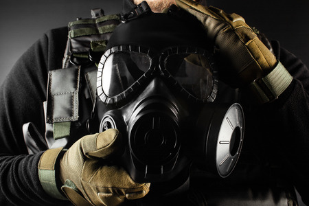 Photo of a fully equipped soldier in black armor tactical vest and gloves standing and holding gas mask on black background closeup front view.