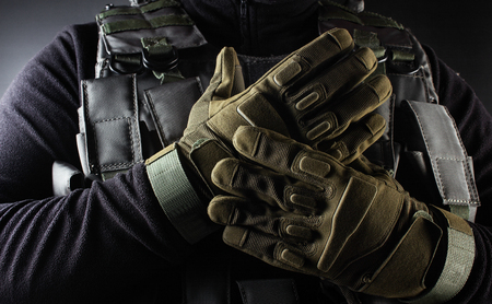 Photo of a fully equipped soldier in black armor tactical vest and gloves standing on black background closeup front view. 版權商用圖片
