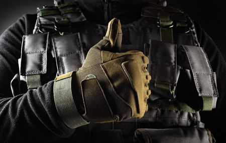 Photo of a fully equipped soldier in black armor tactical vest and gloves standing and showing like on black background closeup front view.