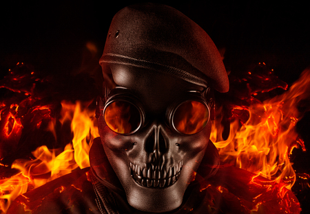 Photo of a fully equipped soldier in black armor tactical vest standing in skull mask and beret on black background with flying ashes and fire closeup front view.