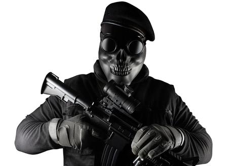 Photo d'un soldat entièrement équipé en gilet d'armure noire debout dans un masque de crâne, un fusil, des lunettes et un béret isolé sur fond blanc vue de face.