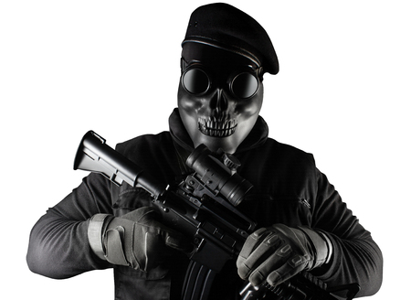 Photo of a fully equipped soldier in black armor vest standing in skull mask, rifle, glasses and beret isolated on white background front view. Stock Photo