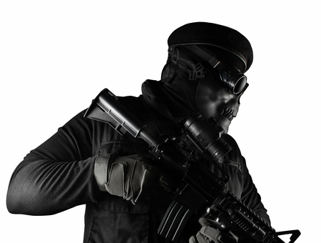Photo of a fully equipped soldier in black armor vest standing in skull mask, rifle, glasses and beret isolated on white background side view. Stock Photo
