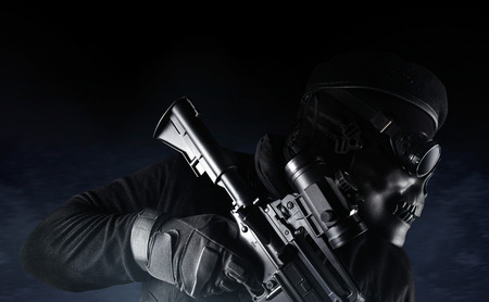 Photo of a fully equipped soldier in black armor vest standing in skull mask, glasses, rifle and beret on dark blue mist background side view. Stock Photo