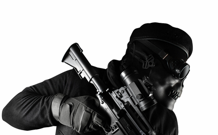 Photo of a fully equipped soldier in black armor vest standing in skull mask, glasses, rifle and beret isolated on white background closeup side view.