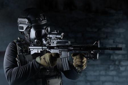 Foto de un soldado totalmente equipado con chaleco táctico de armadura negra, máscara de gas, rifle automático, guantes y casco apuntando a la vista de perfil sobre fondo de ladrillo negro.