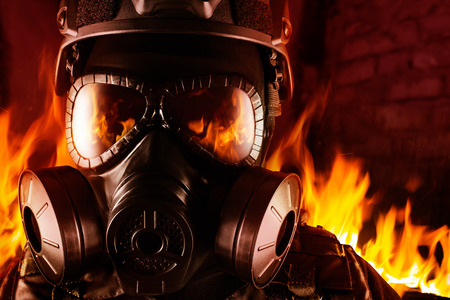 Photo of a fully equipped soldier in black armor tactical vest, gas mask standing in fire on brick background closeup front view. Stock Photo