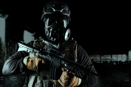 Photo of a fully equipped soldier in black armor tactical vest, gas mask, automatic rifle, gloves and helmet on dark ruined background. Stock Photo