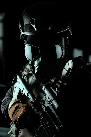 Photo of a fully equipped soldier in black armor tactical vest, gas mask, automatic rifle, gloves and helmet standing on black background closeup view. Stock Photo