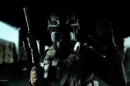 Foto eines voll ausgestatteten Soldaten in schwarzer Rüstung, taktischer Weste, Gasmaske, automatischem Gewehr, Handschuhen und Helm, der taktisches Zeichen auf schwarzem Hallenhintergrund zeigt.