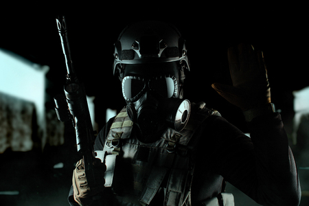 Photo of a fully equipped soldier in black armor tactical vest, gas mask, automatic rifle, gloves and helmet standing and showing tactical sign on black hall background.