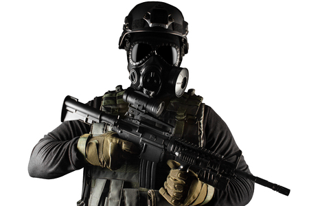 Photo of a fully equipped soldier in black armor tactical vest, gas mask, automatic rifle, gloves and helmet front view isolated on white background.