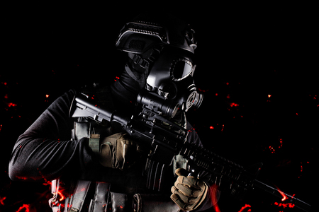 Photo of a fully equipped soldier in black armor tactical vest, gas mask, automatic rifle, gloves and helmet aiming profile view standing in ashes on black background.
