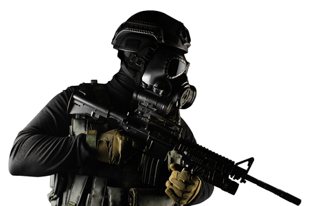 Photo of a fully equipped soldier in black armor tactical vest, gas mask, automatic rifle, gloves and helmet standing isolated on white background.