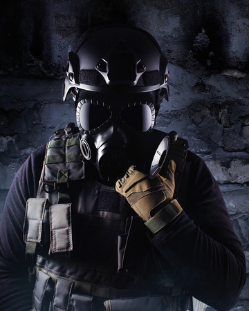 Photo of a fully equipped soldier in black armor tactical vest, gas mask, gloves and helmet standing on shaded brick wall background. Stock Photo