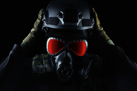 Photo of a fully equipped soldier in black armor tactical vest, gas mask with red eyes, gloves and putting on helmet standing on black background closeup view.