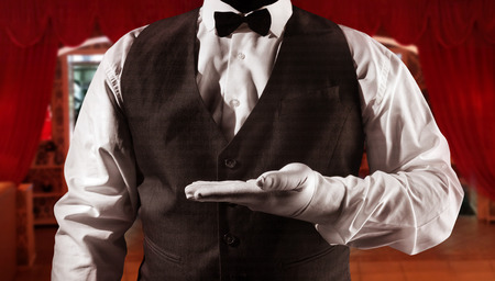 Photo of a waiter in white shirt and black waistcoat showing hand copyspace on shaded red restaurant background torso view.