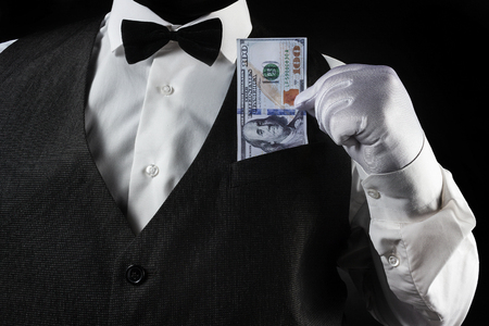 Photo of a waiter in white shirt and black waistcoat pulling out dollar banknote in white glove on black background torso view.