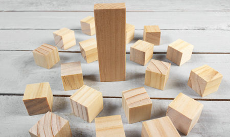 Concept photo of a small wooden blocks surrounding a bigger block on table surface background.