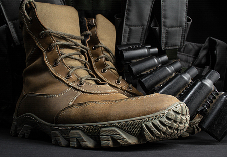 Photo of brown suede military tactical boots standing with armor vest and cartridge belt on black surface background.