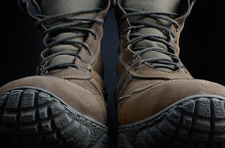 Photo of brown suede military tactical boots standing on black surface background front view.