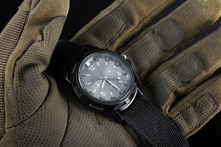Photo of a first person view arm in tactical gloves holding black military watch on black background close up view.