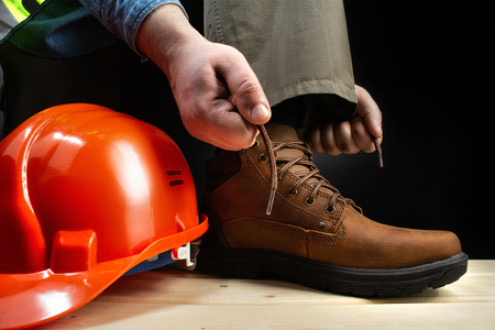 Photo of a worker lacing up leather boot on a surface with protective helmet. Reklamní fotografie - 125952884
