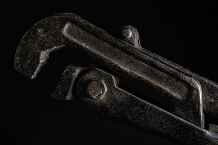 Photo of an old adjustable wrench close up photo on black background. Stock Photo