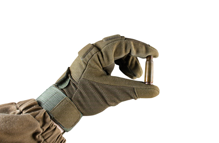 Isolated photo of a first person view arm in tactical jacket and gloves holding Ak 47 rifle bullet shell on white background.