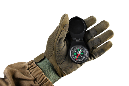 Isolated photo of a first person view arm in tactical jacket and gloves holding black compass on white background.