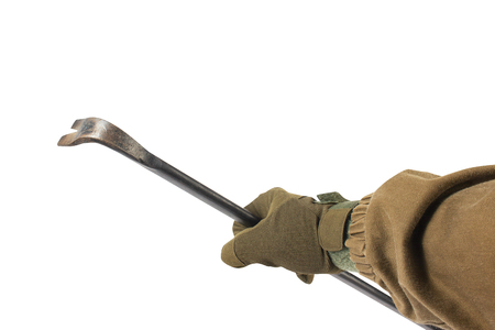 Isolated photo of a first person view arm in tactical jacket and gloves holding crowbar on white background. Stock Photo
