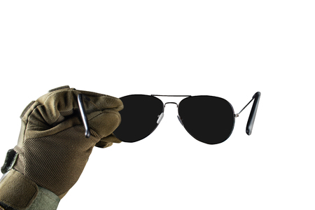 Isolated photo of a first person view arm in tactical jacket and gloves holding black sunglasses on white background. Stock fotó