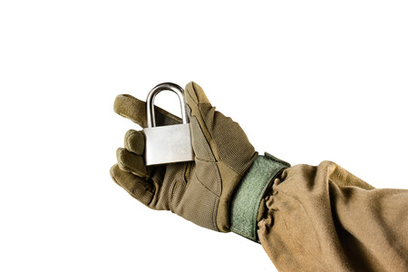 Isolated photo of a first person view arm in tactical jacket and gloves holding closed steel lock on white background. Stock fotó