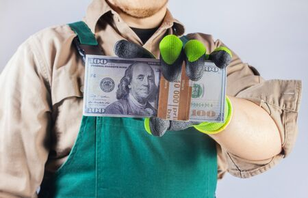 Photo of a worker in green overall outfit with protective gloves holding pack of dollar banknotes, torso view.