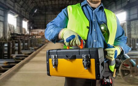 Worker in jeans shirt, green jacket, glasses, tool belt and protective gloves holding a yellow toolbox on factory area background.