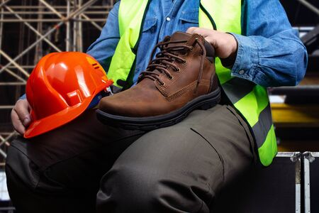 Photo of a worker in green jacket sitting with leather boot and protective helmet on construction area background. Stock Photo