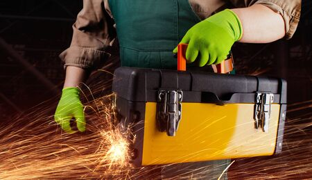 Photo of a worker in green overall outfit with protective gloves holding yellow toolbox with sparks torso view on black construction area background.