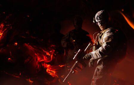Photo d'un soldat entièrement équipé posant avec un fusil automatique avec une lunette en feu, des cendres et des silhouettes en arrière-plan.