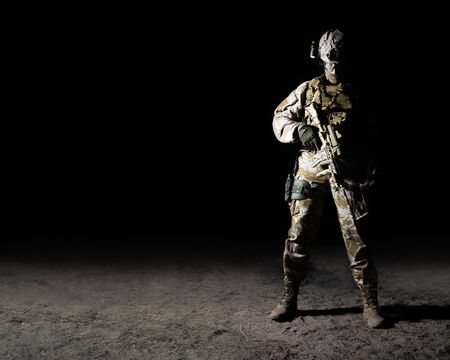 Photo of a fully equipped soldier standing with automatic rifle with scope on a sand desert ground on dark background full body front view.